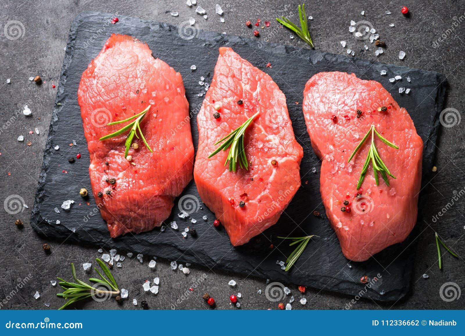 Bifteck de boeuf avec le romarin et les épices sur le fond noir