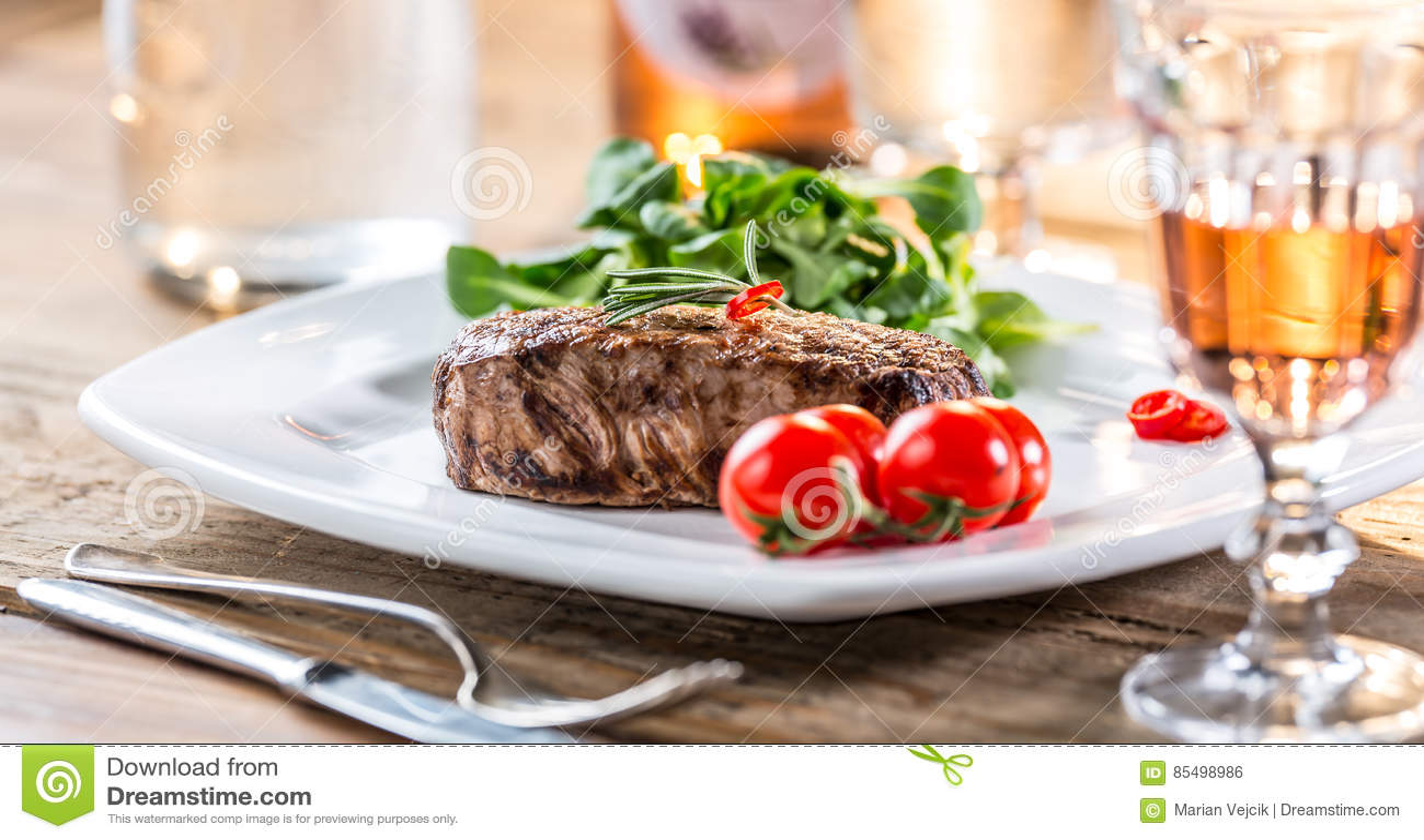 Bifteck de boeuf bifteck juteux de boeuf Bifteck gastronome avec les légumes et le verre de vin rosé sur la table en bois