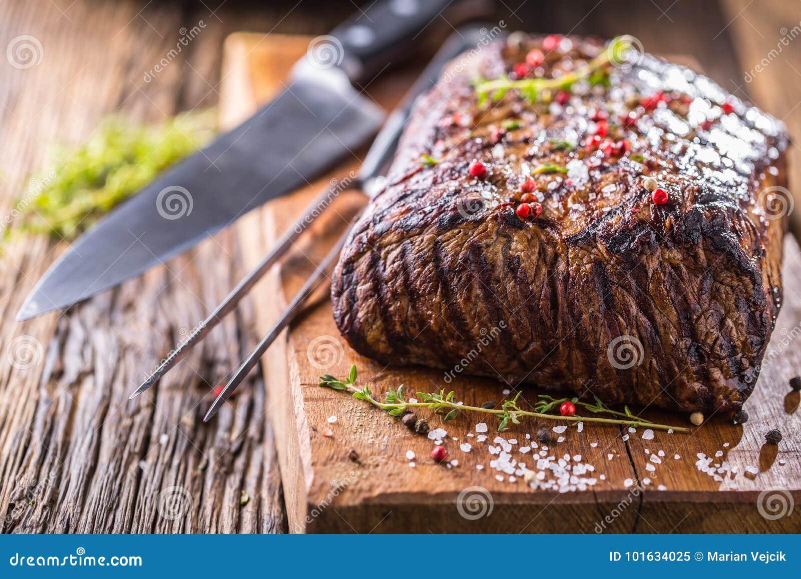 Bifteck de boeuf Bifteck juteux de Rib Eye dans la casserole sur le conseil en bois avec l herbe et le poivre
