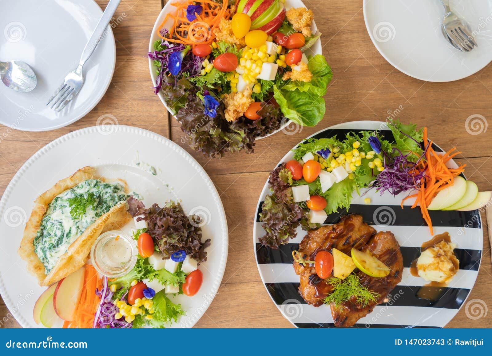 Bifteck de poulet, épinards cuits au four avec le roti de fromage, et salade sur une table en bois