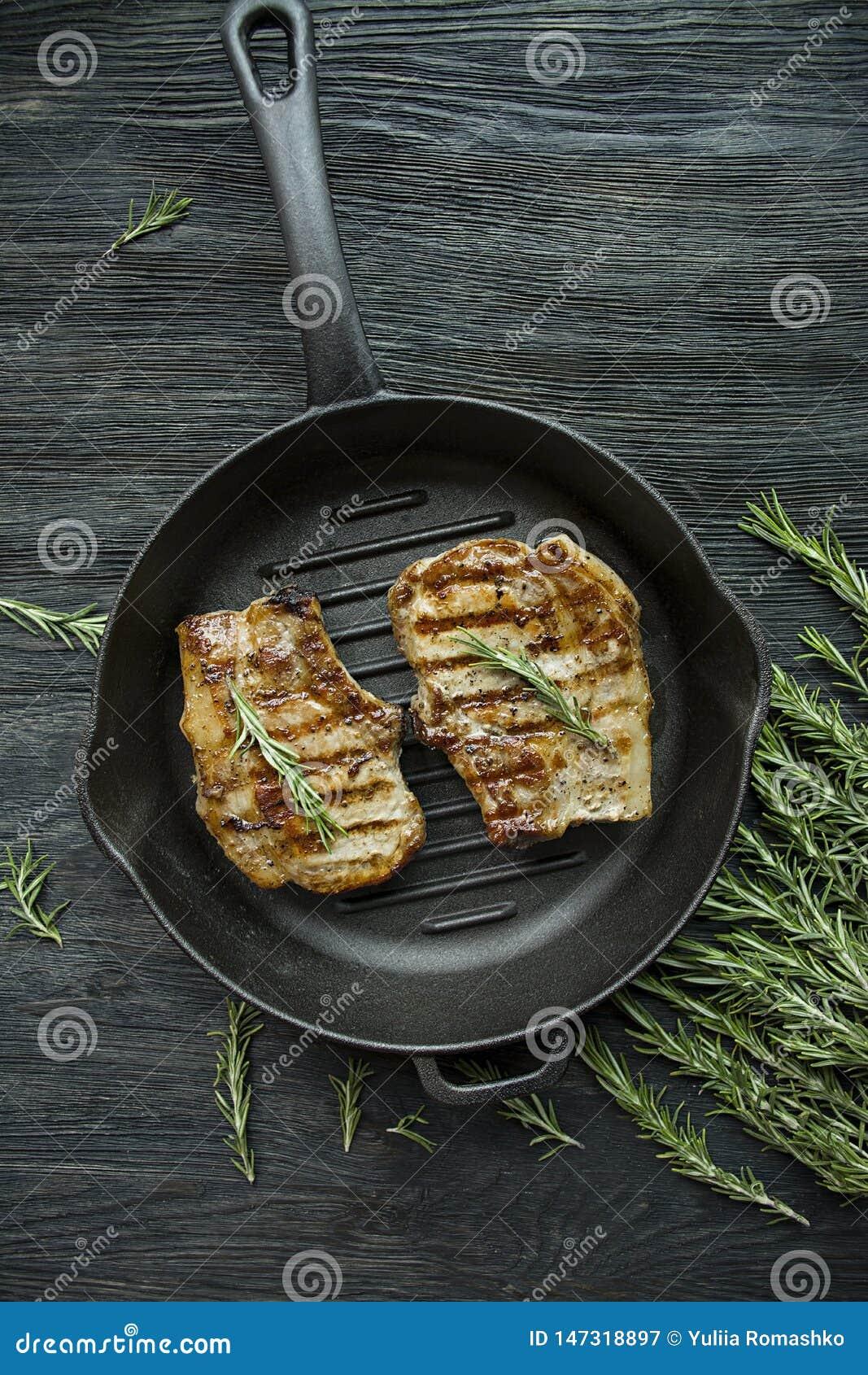 Bifteck grillé sur une casserole ronde de gril, garnie avec des épices pour la viande, le romarin, les verts et les légumes sur u