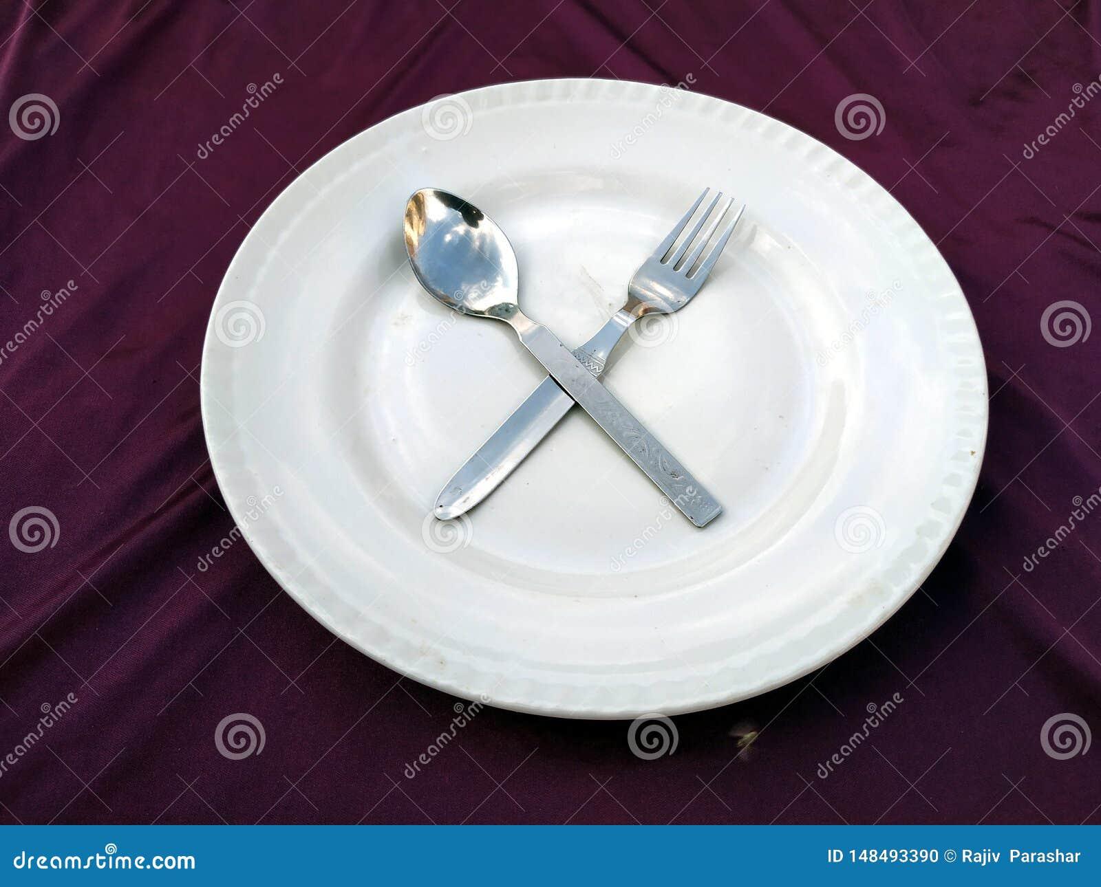 Bifurcaci?n y cuchara en la placa blanca aislada en un fondo violeta