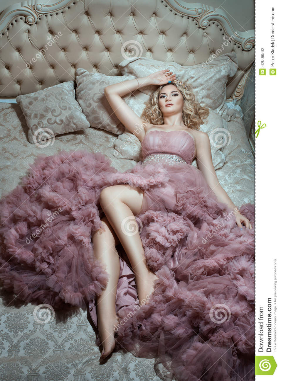 On The Big Bed Is Girl In A Magnificent Dress Stock Photo