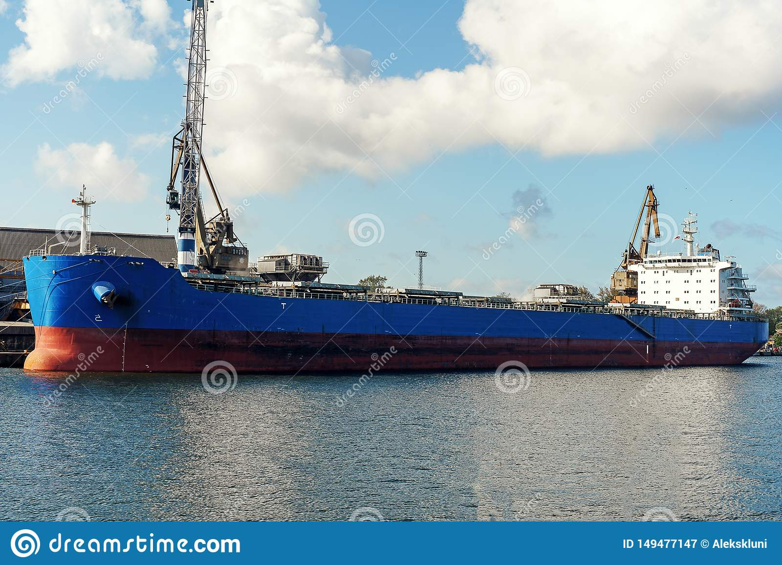 Big blue bulker cargo ship moored in the cargo port during cargo operation.