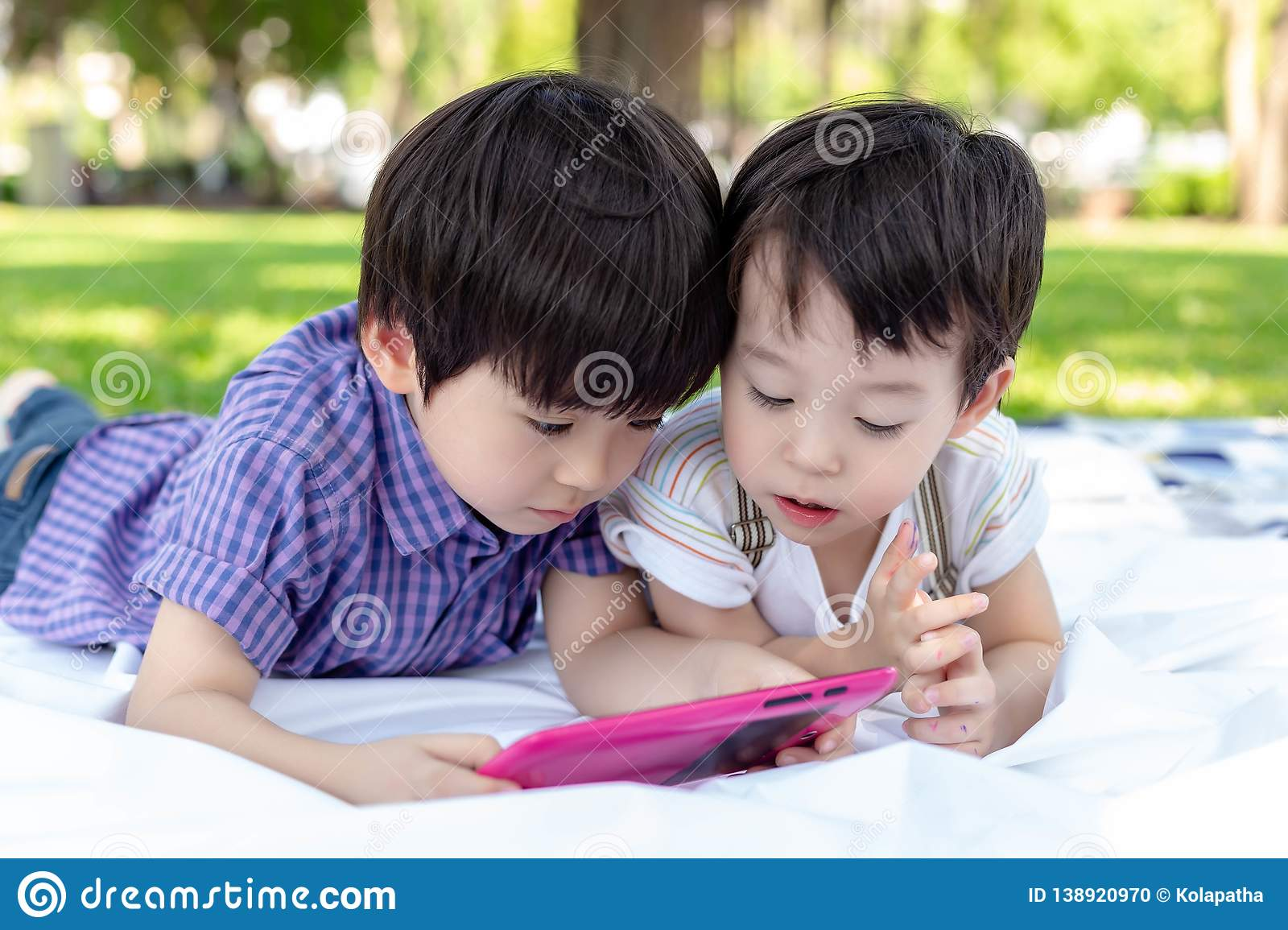 Big brother and younger brother are watching cartoons on tablet at park. Cute young boys are brotherhood. Lovely children always