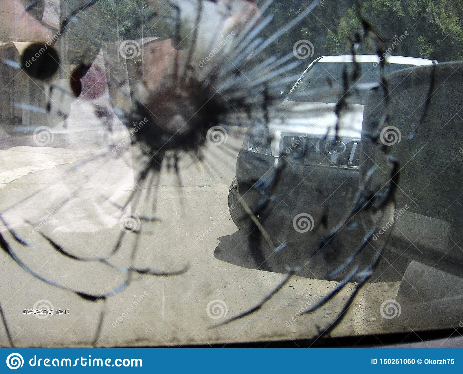 Big crack to windshield of car from fragment military sniper bullet