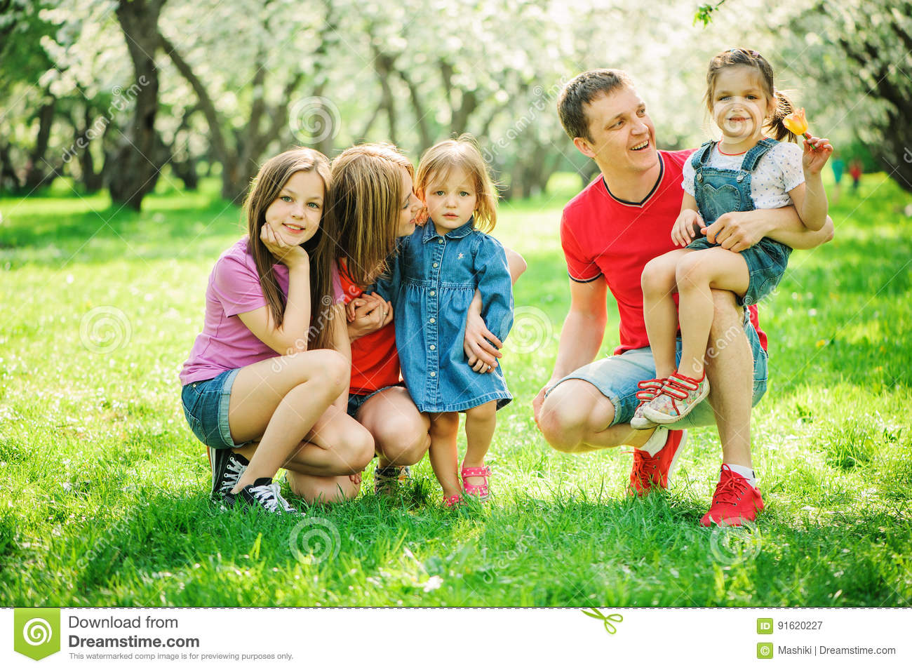 Big family with three little daughters spending time together in summer park, mother, father and sisters having fun
