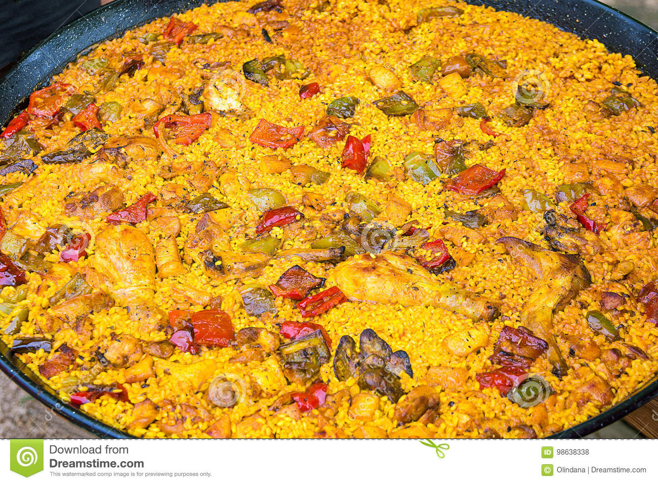 Big flat frying pan with home cooked Spanish paella. Variety of meat chicken, rabbit, vegetables, rice, tomato sauce, spices