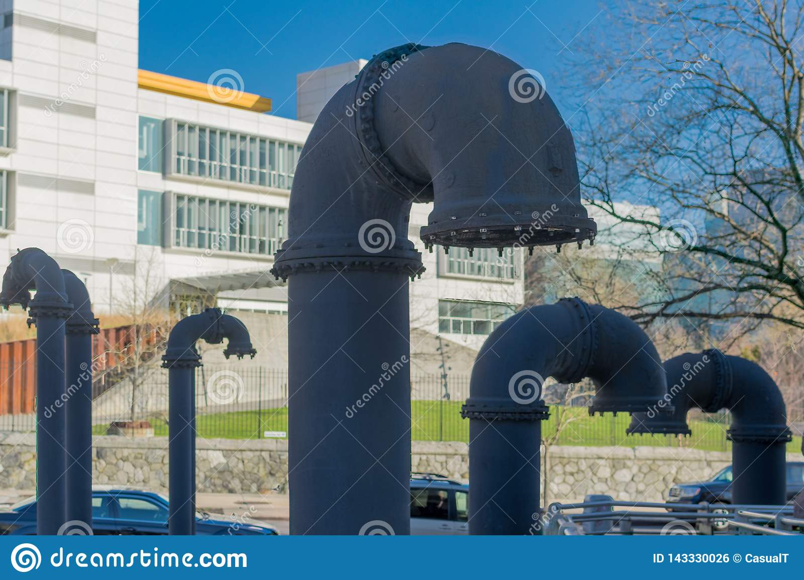 Big grey industrial pipes, sticking out of the ground