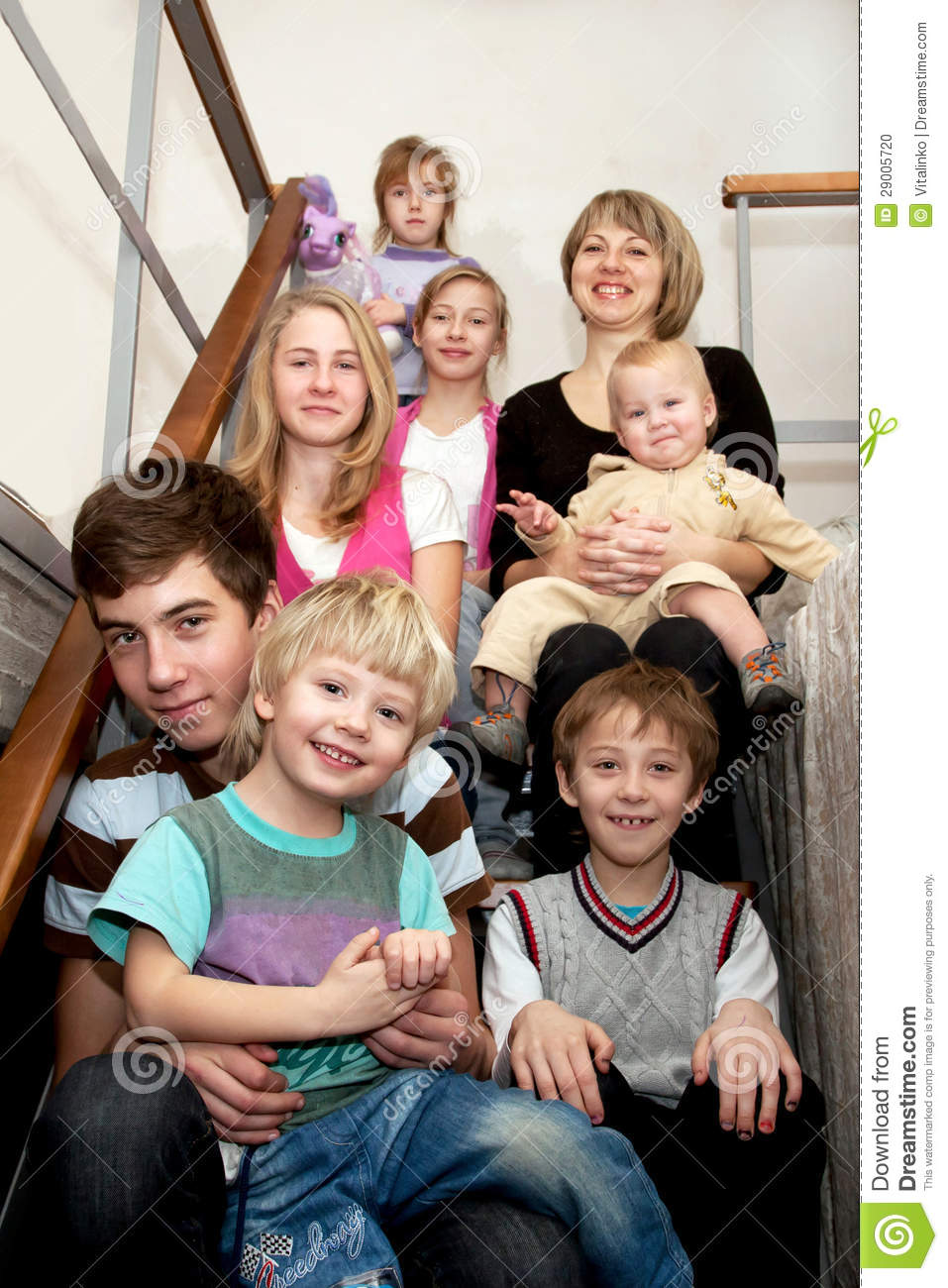 Big happy family sitting on the stairs at home.