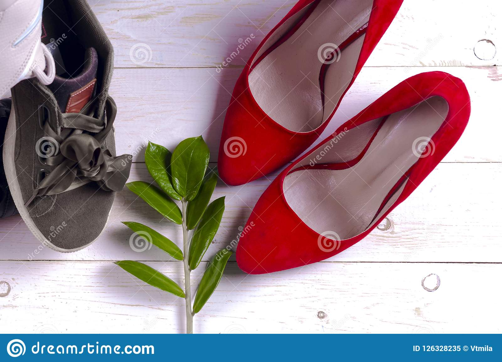 be8d9edc07da Big heap of different sports shoes and red high heel women`s shoes on white