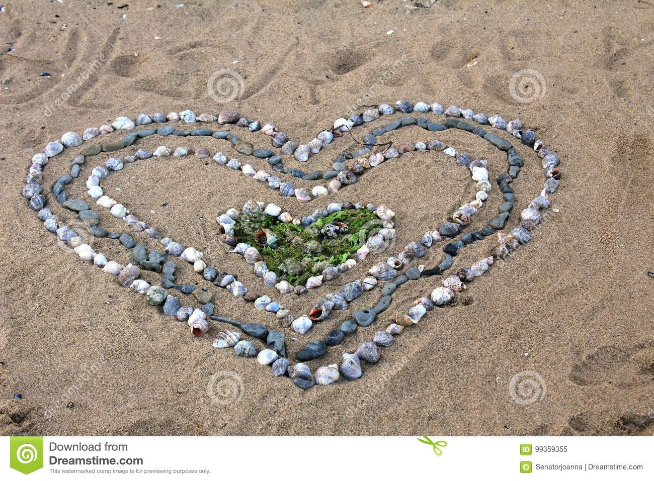 Big heart made of little seashells on the sandy beach on the black royalty free stock photo buycottarizona Images