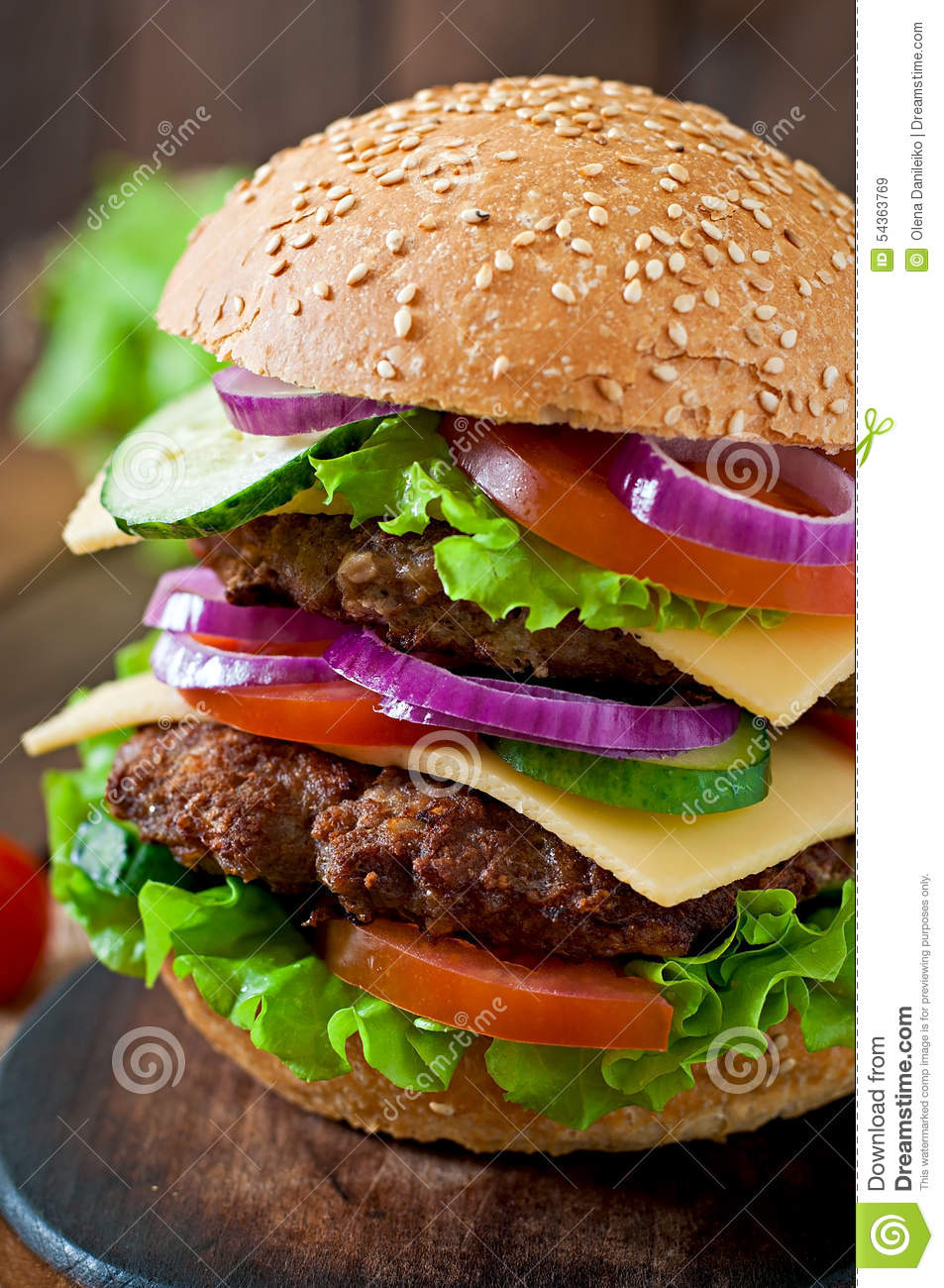 Big Juicy Hamburger With Vegetables On A Wooden Background