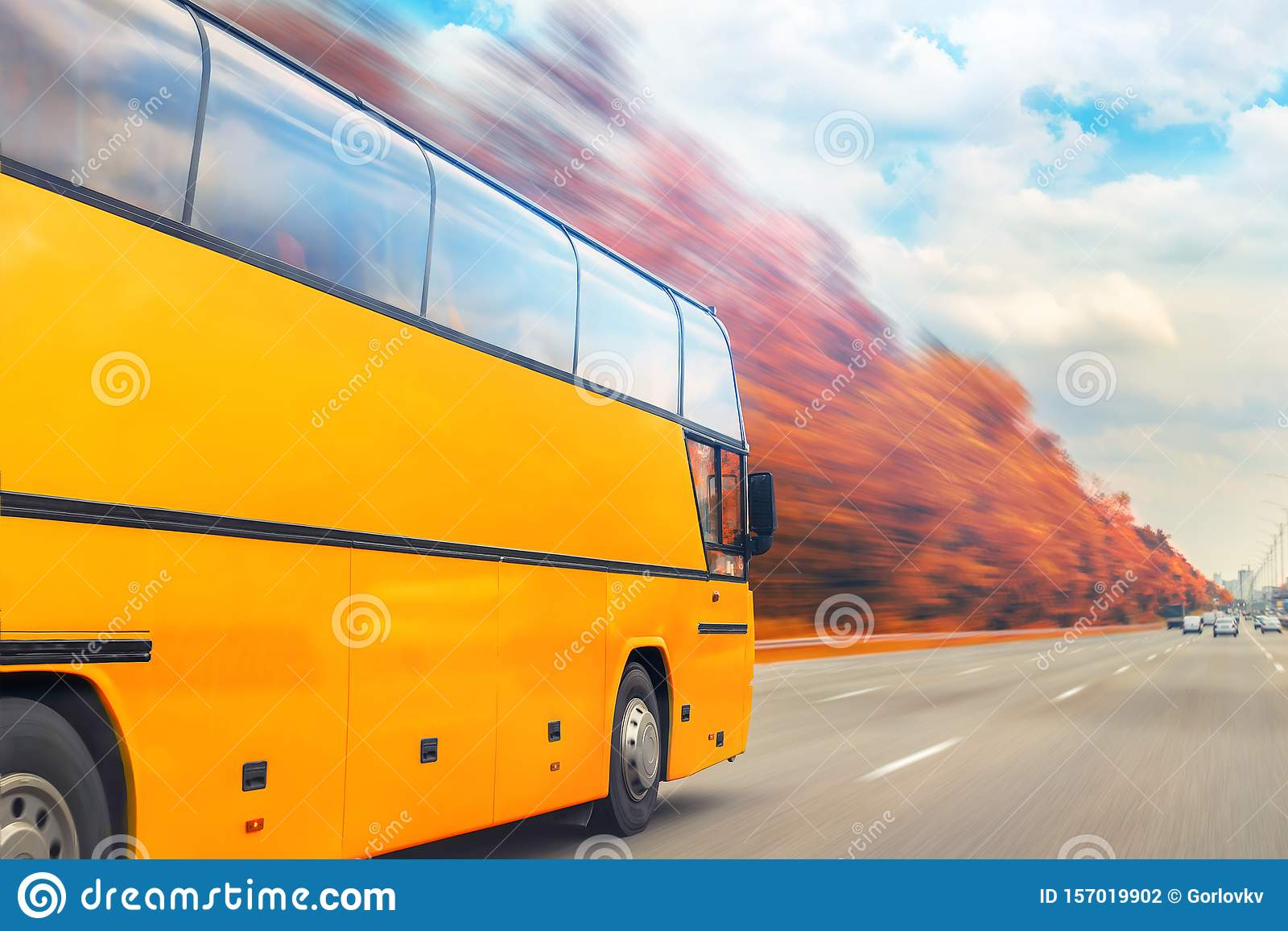 Big luxury comfortable tourist bus driving through golden autumn tree highway on bright sunny day. Blurred motion.Travel and coach