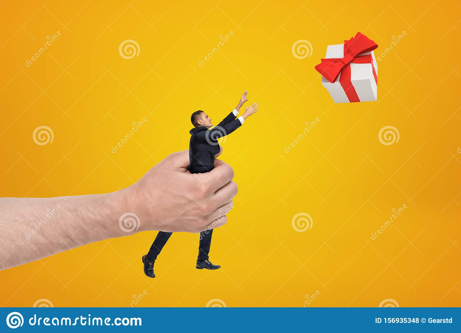 Big male hand holding businessman reaching out to gift box on yellow background