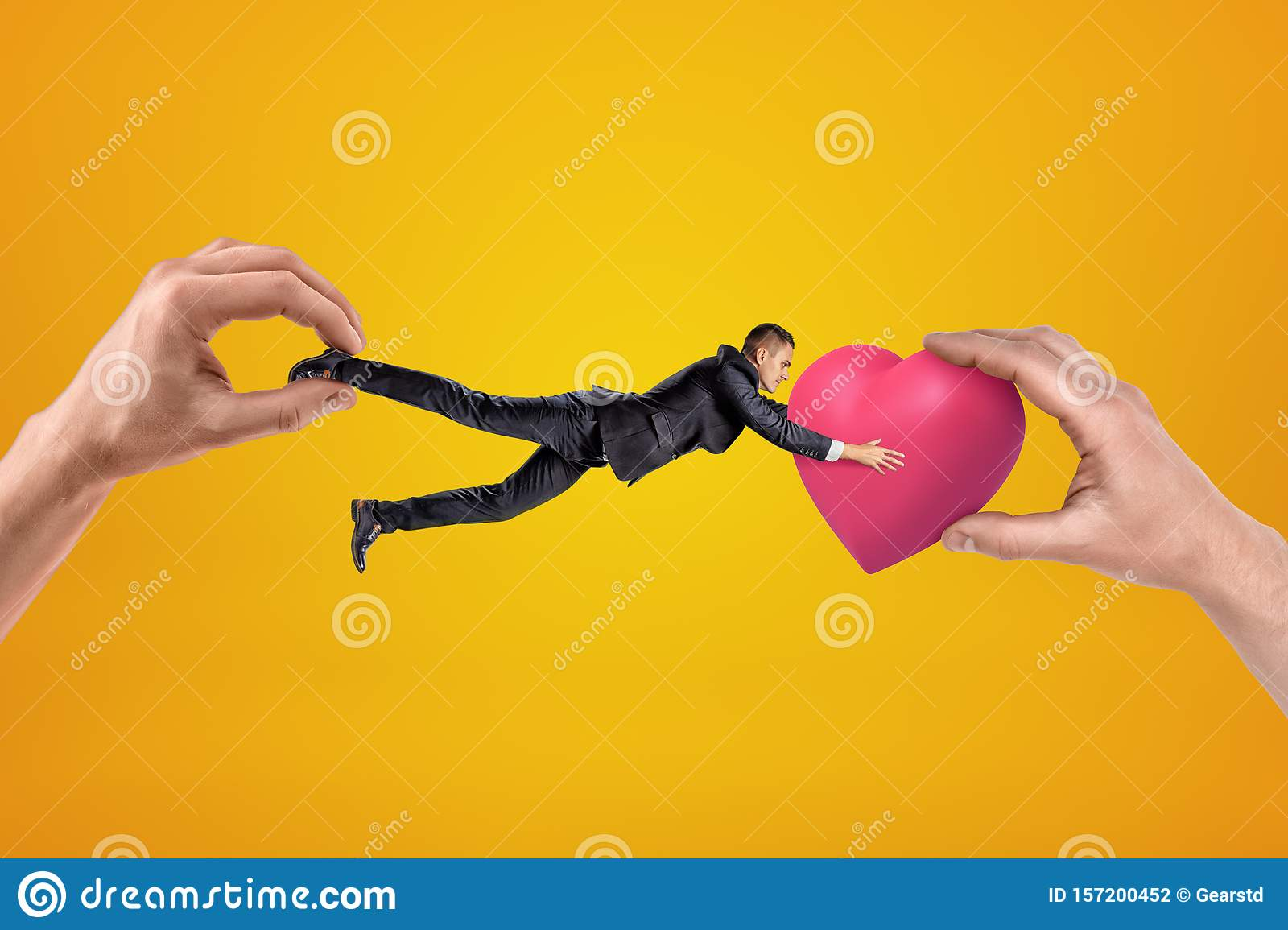 Big male hand holding tiny businessman who is reaching to another big hand holding pink heart on yellow background