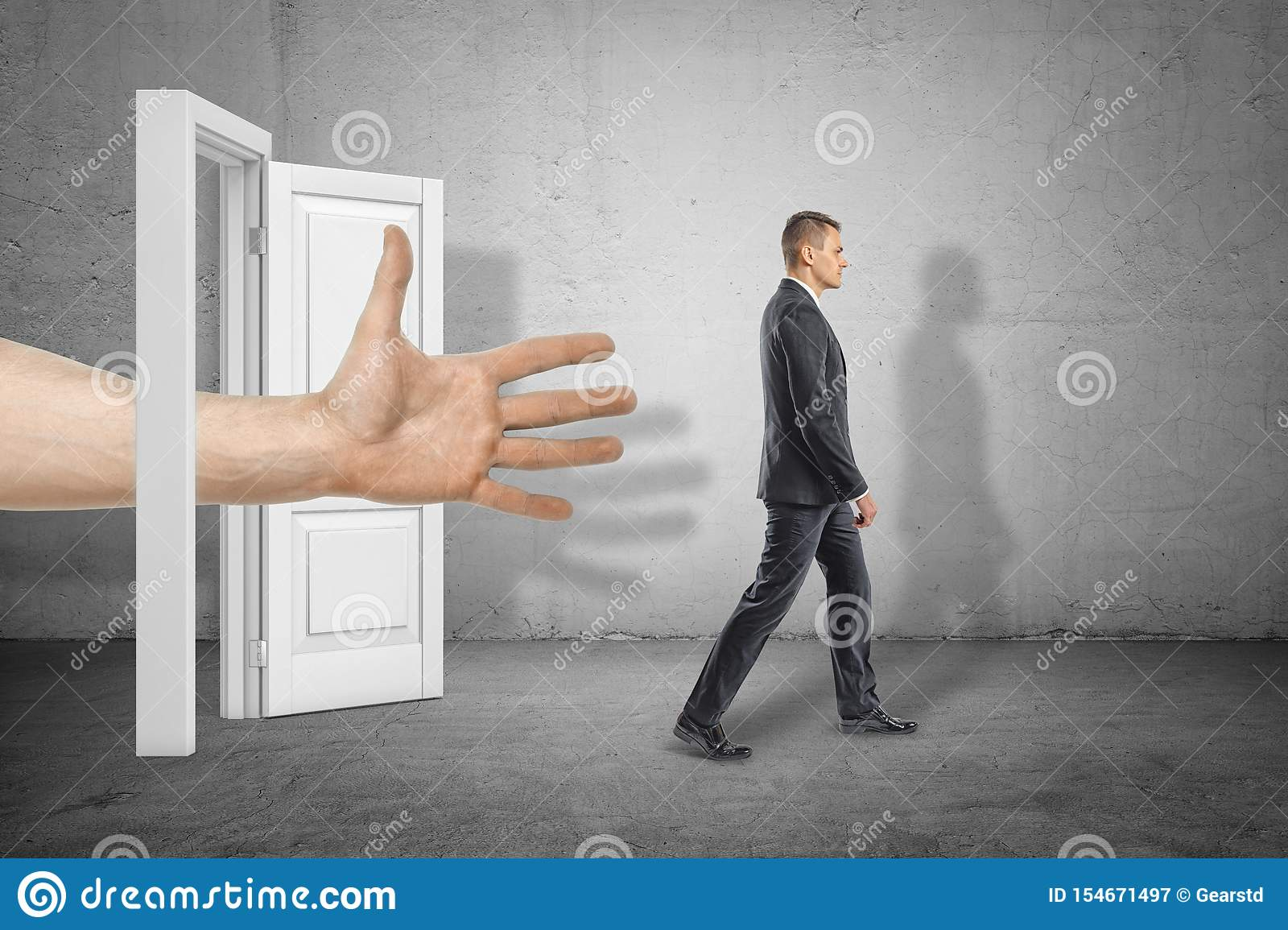 Big male open hand reaching through white doorway to young businessman who is walking away on grey wall background