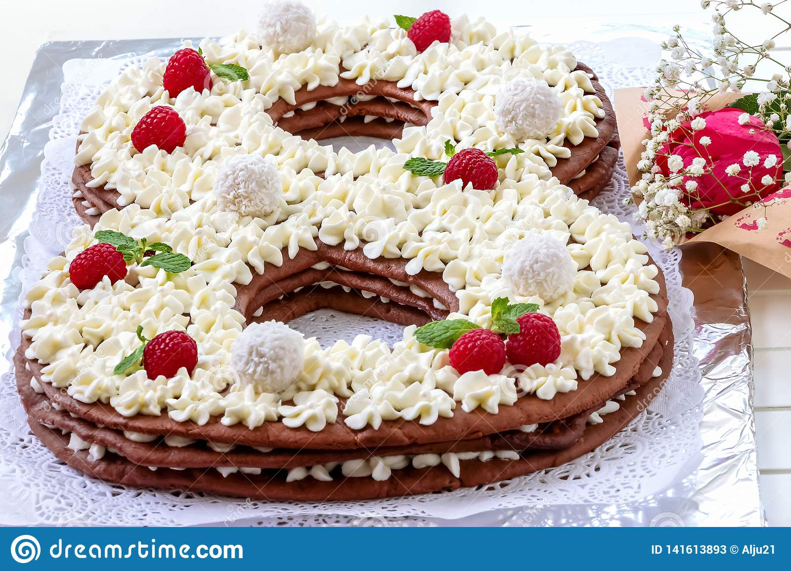 Big number cake and red rose flower. Cake shape of number 8 decorated white creamcheese, raspberry and coconut candy.