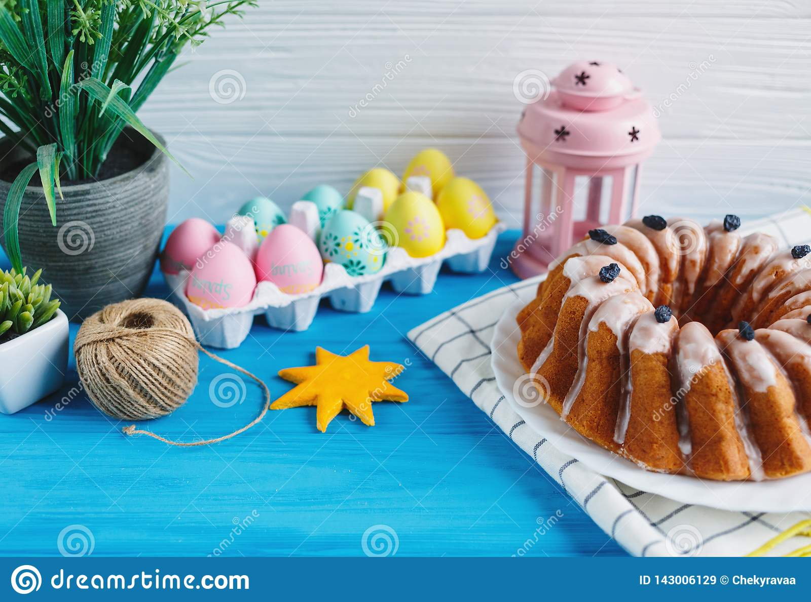 Big plate with cake and hand painted colorful eggs, on towel on blue background. Close up. Decoration for Easter,