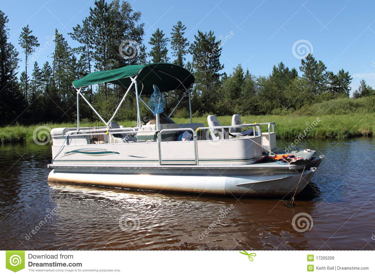 big pontoon boat anchored in the river with fishing poles and the ...
