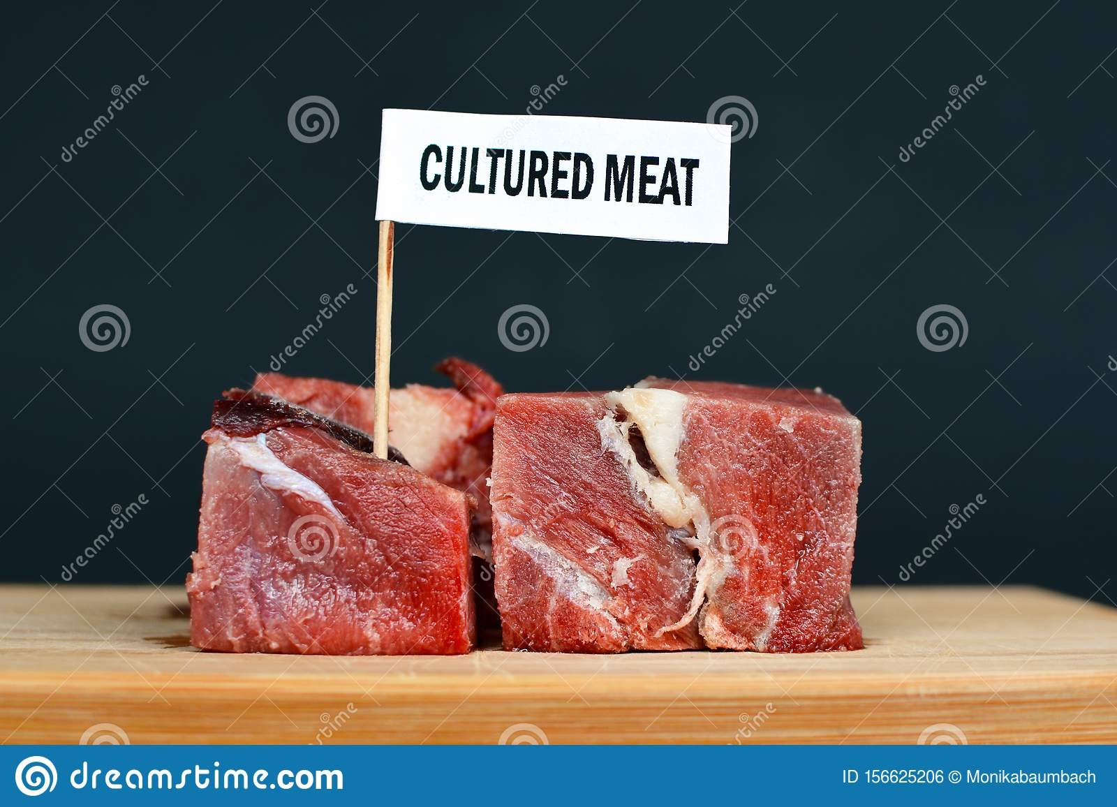 Big raw red meat chunks on wooden plate with label saying `cultured meat`