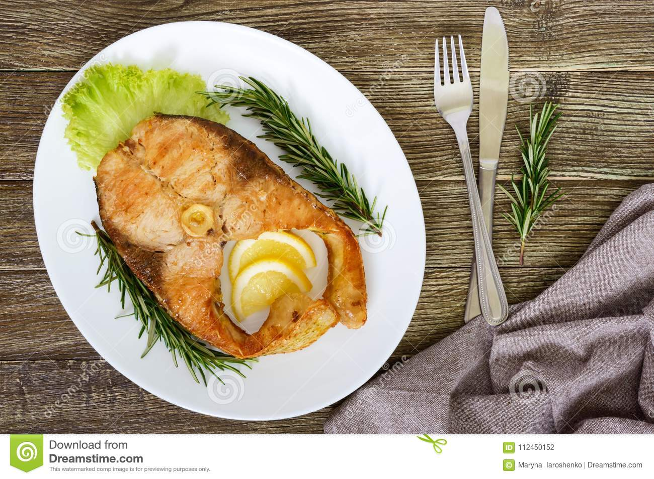 Big roasted carp steak with lemon and rosemary. Top view