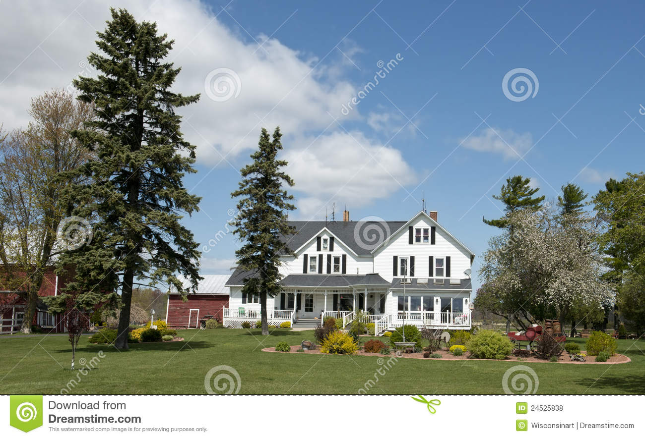 The image the house is painted white and the sky is blue with clouds