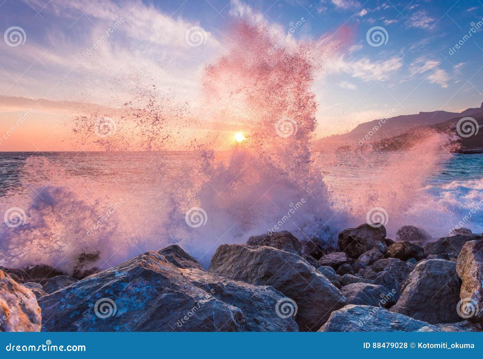 Big sea wave breaks against a stone