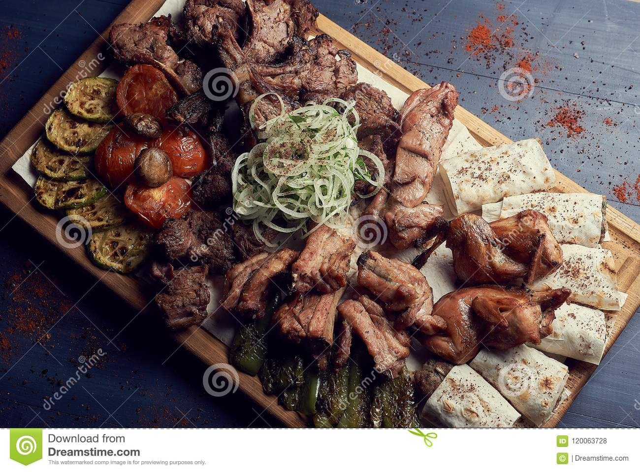 A big set of grilled meat with vegetables on big wooden plato or cutting board on gark wooden background. Tradicional