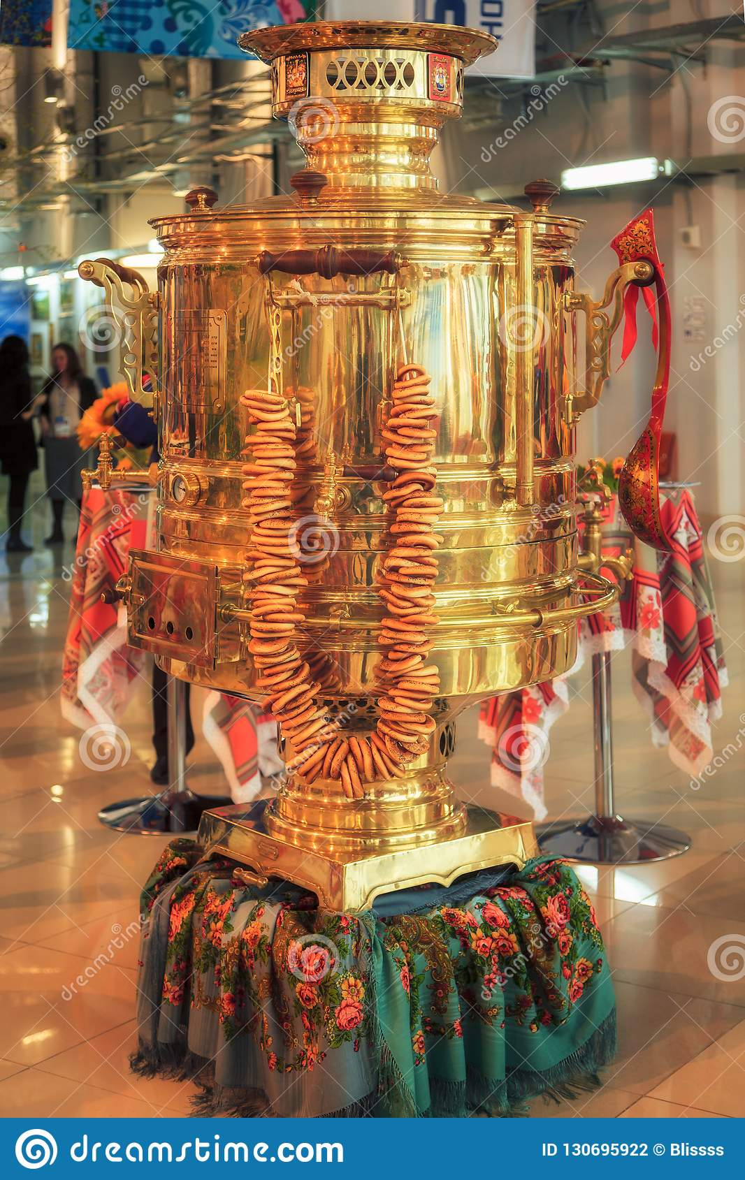 Big shining golden vintage festive Russian samovar with a bunch of bagels set out in the Olympic Mediacenter for quests to admire.