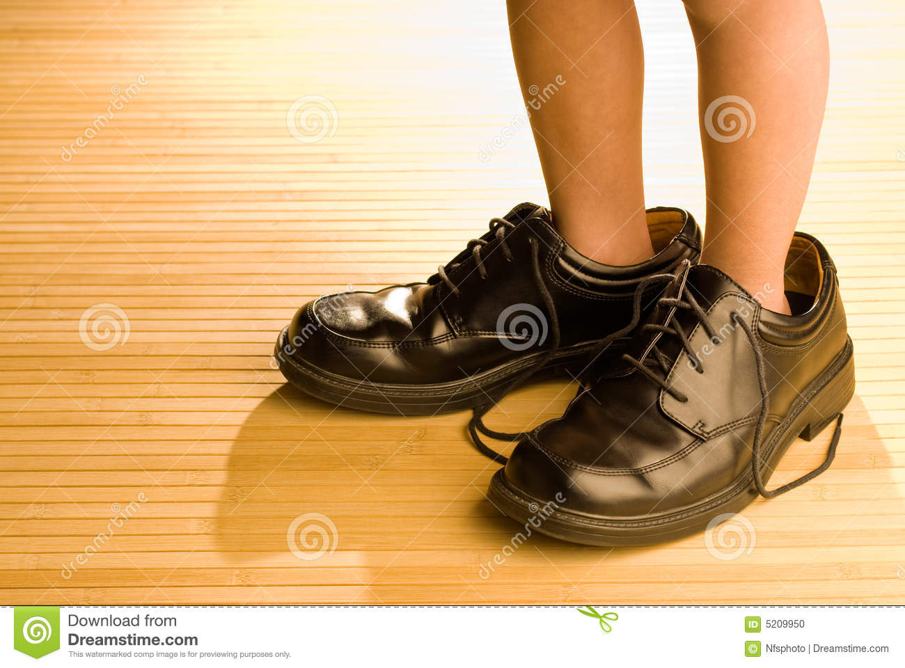 Big shoes to fill, child s feet in large black shoes