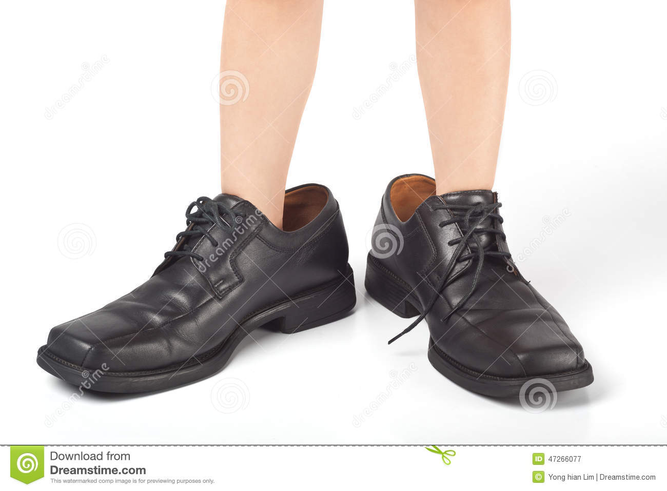 Little kid wearing adult s shoes that are too big