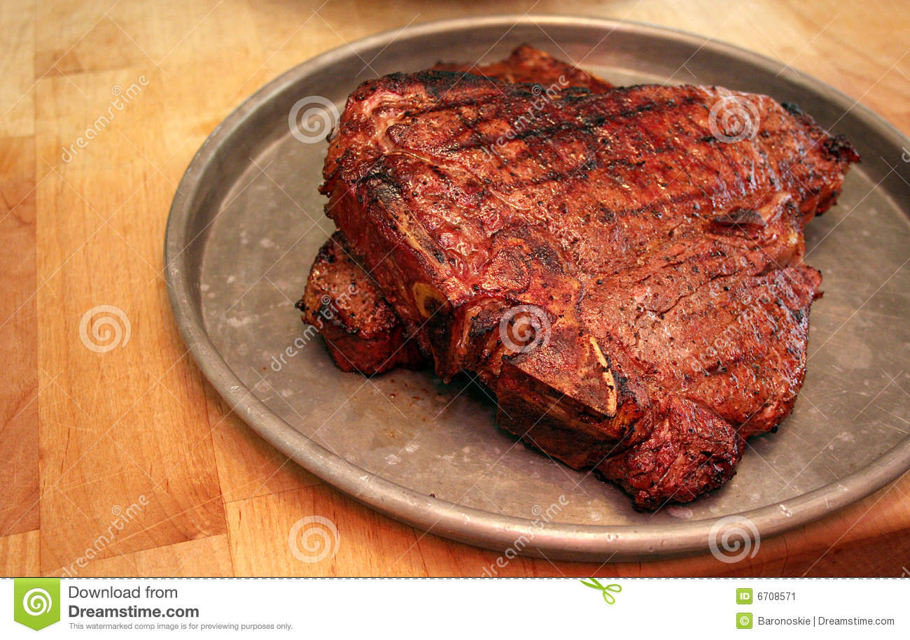 big juicy steak sits on a platter ready to eat.