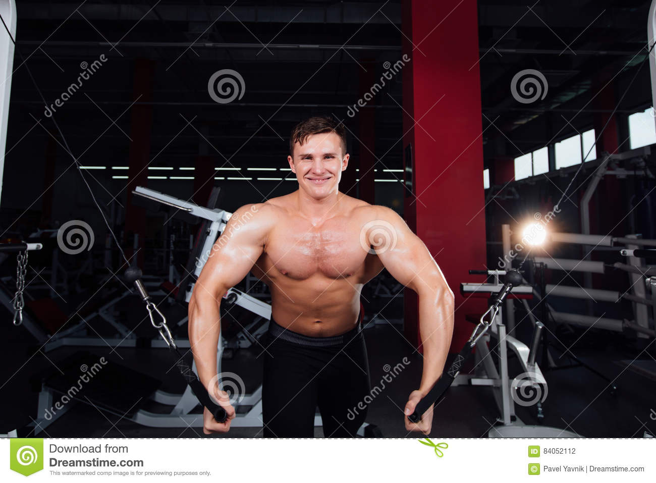 Big strong bodybuider without shirts demonstrate crossover exercises. The pectoral muscles and hard training