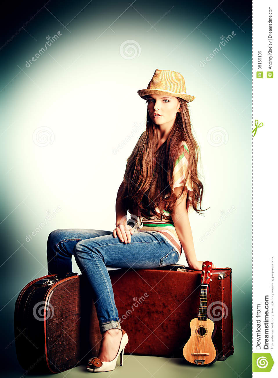 Attractive girl sitting on her old suitcases. Travel and tourism ...