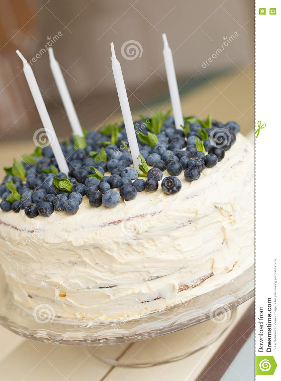 A Big White Birthday Cake With Fresh Organic Blueberries And Mint