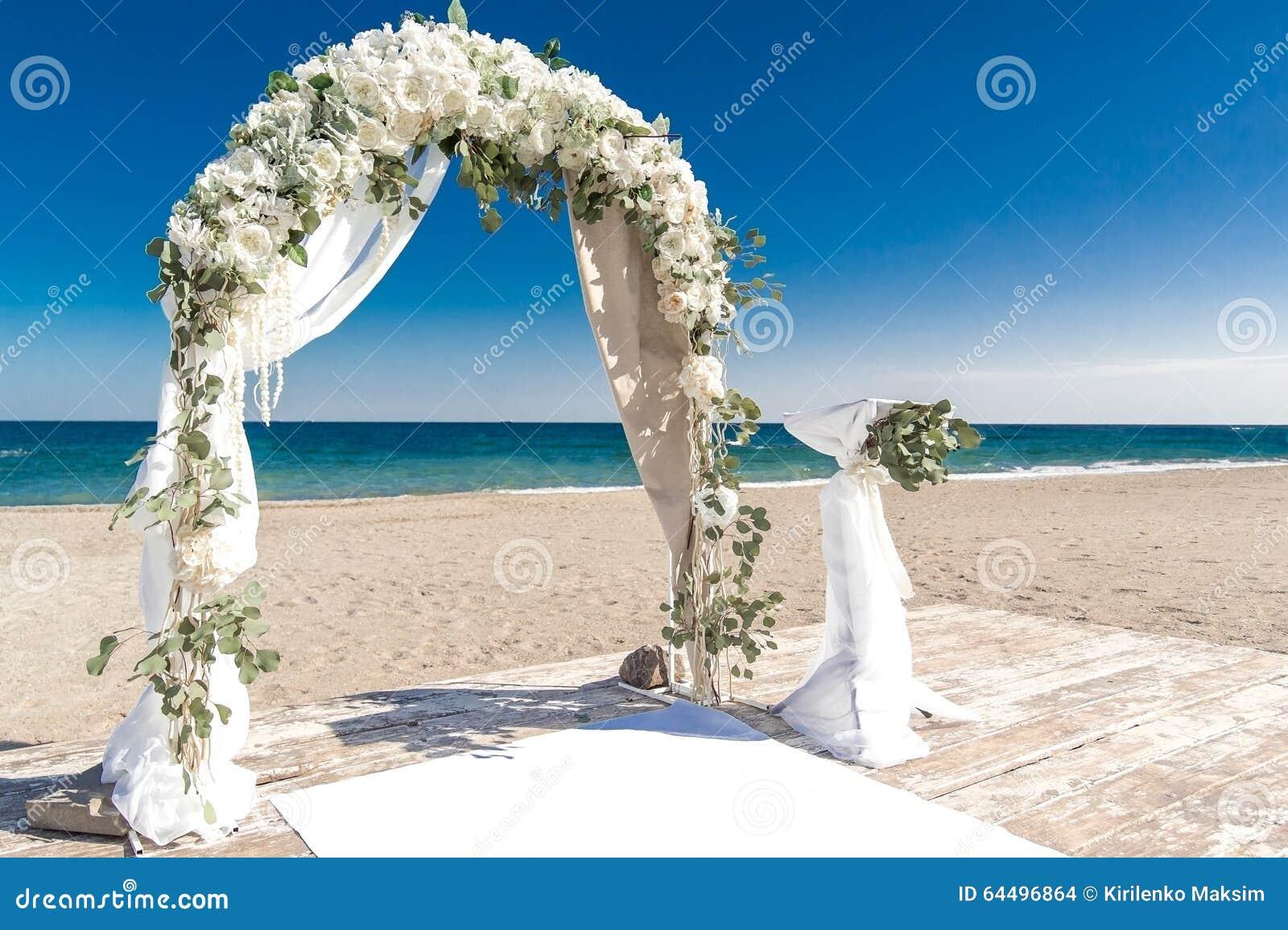 Big white wedding arch at ocean coast