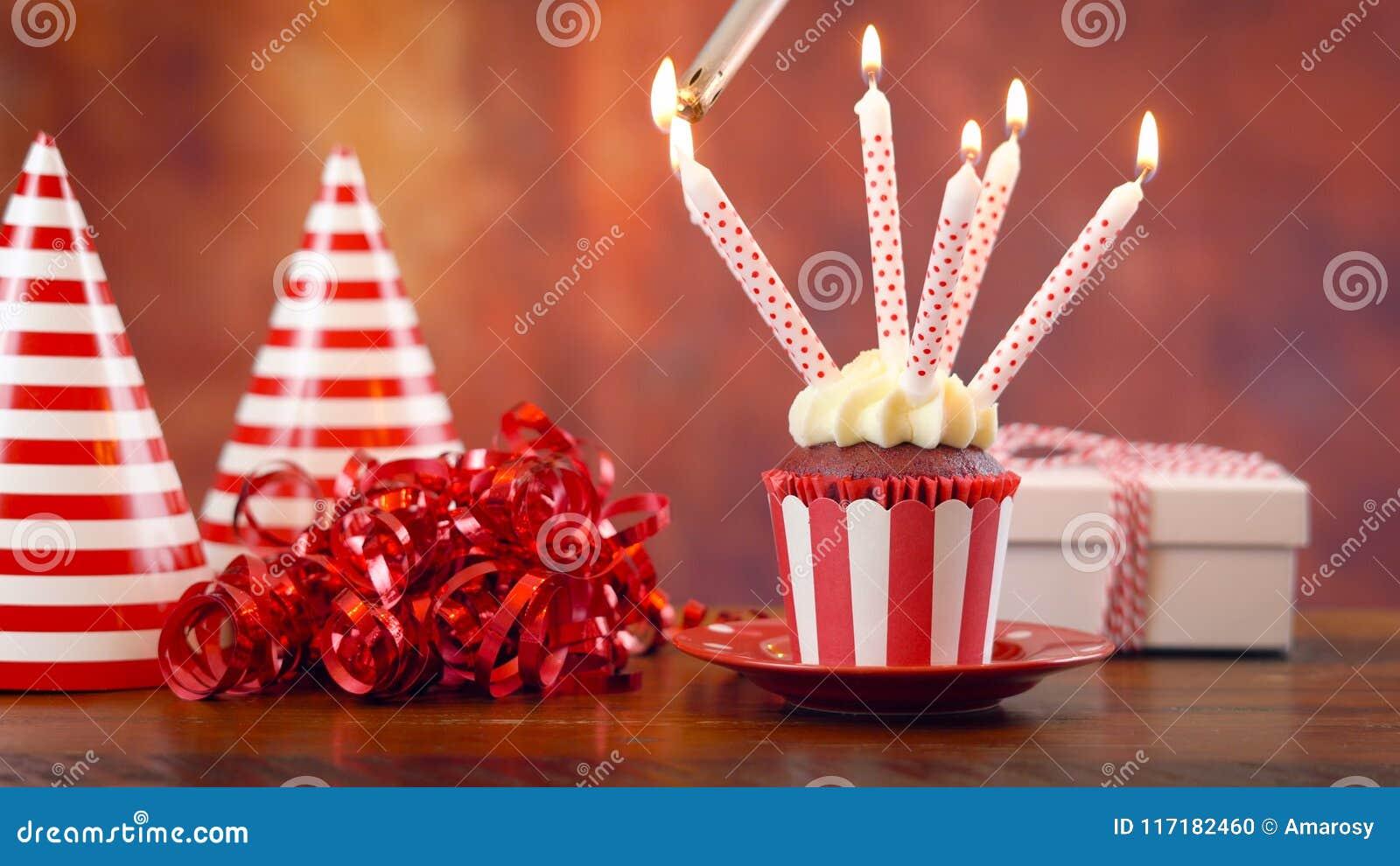 Bigné di compleanno di illuminazione con le candele ed il regalo