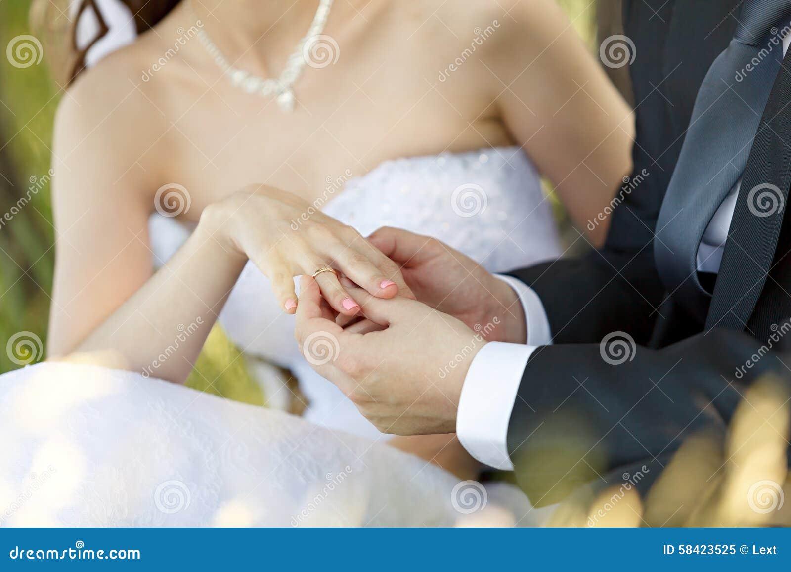 Bij het huwelijk, zet de bruidegom de ring op de vinger van de bruid
