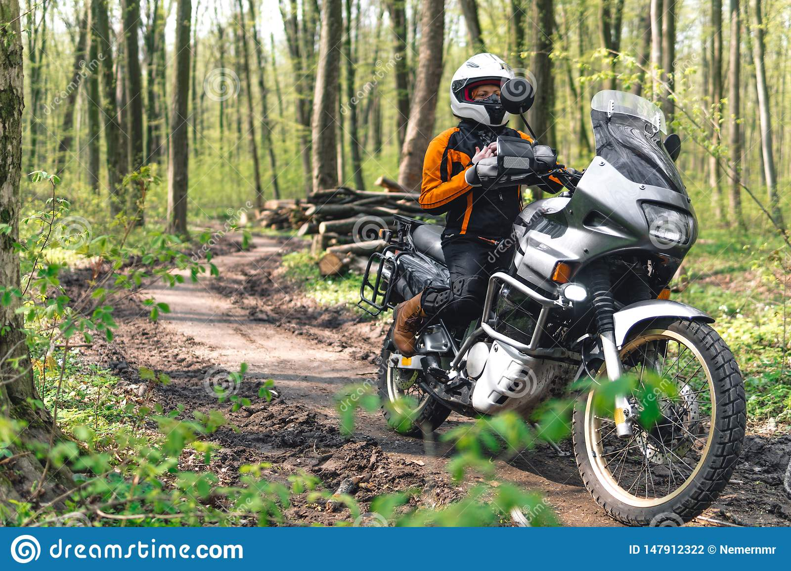Biker girl wearing a motorcycle outfit, protective clothing, equipment, adventure touristic motorbike with side bags. outdoor