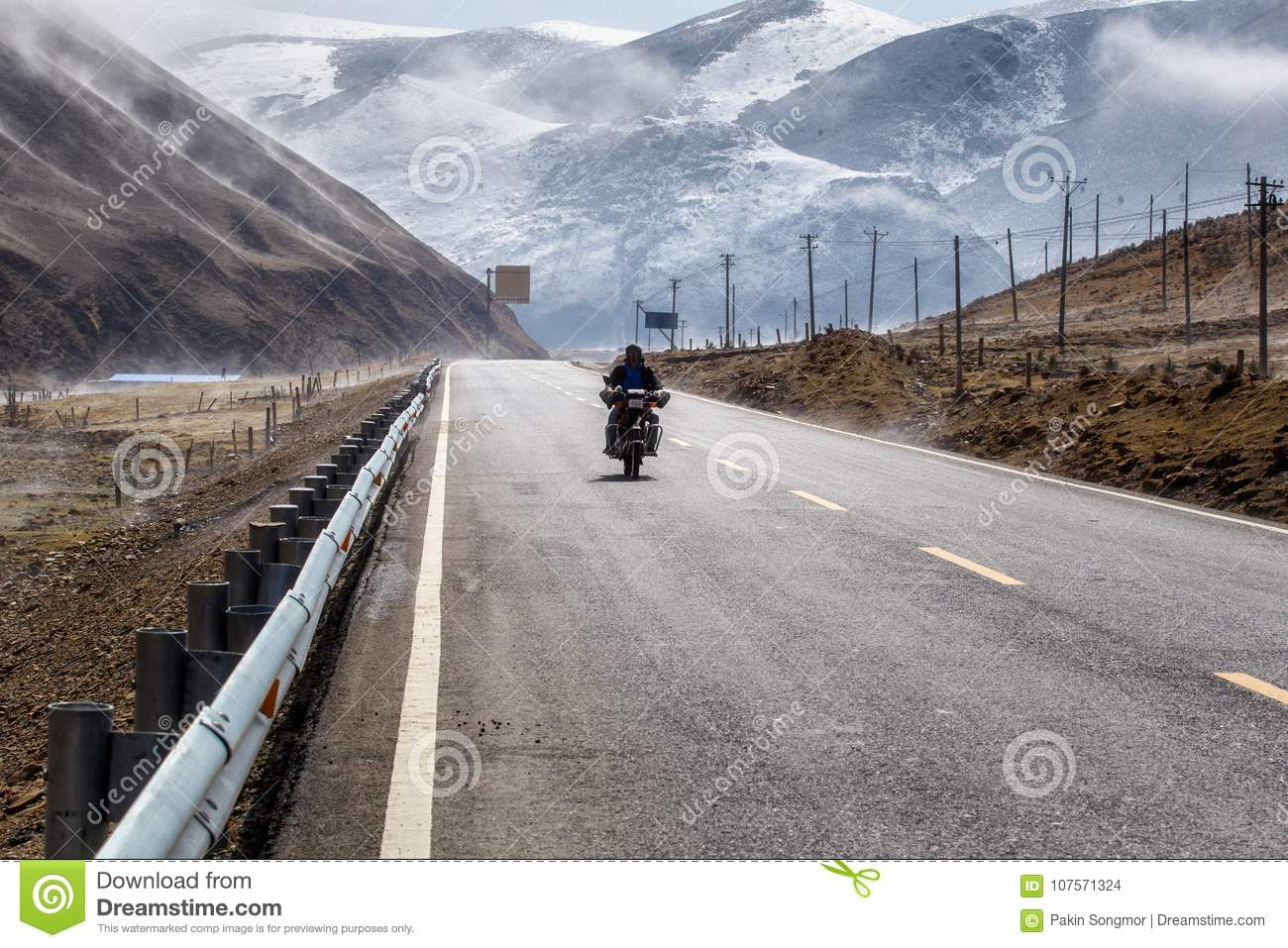 Biker motorcycle on the road beautiful winter in Tibet under snow mountain