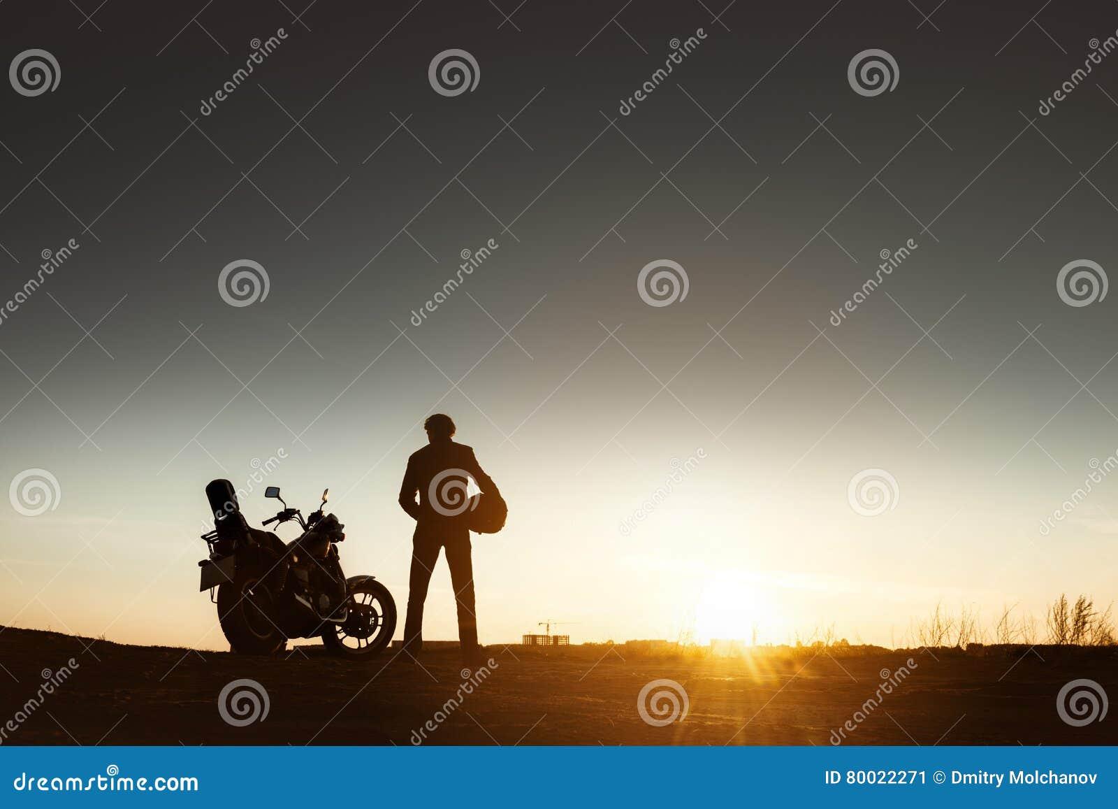 Biker& x27; s sylwetka z motocyklu zmierzchem