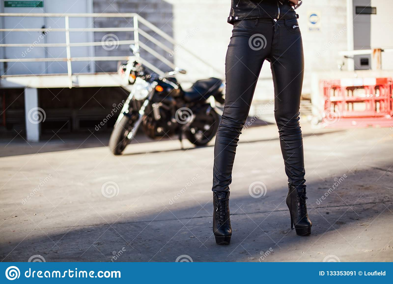 Biker Woman In Leather Jacket Standing In Front Of