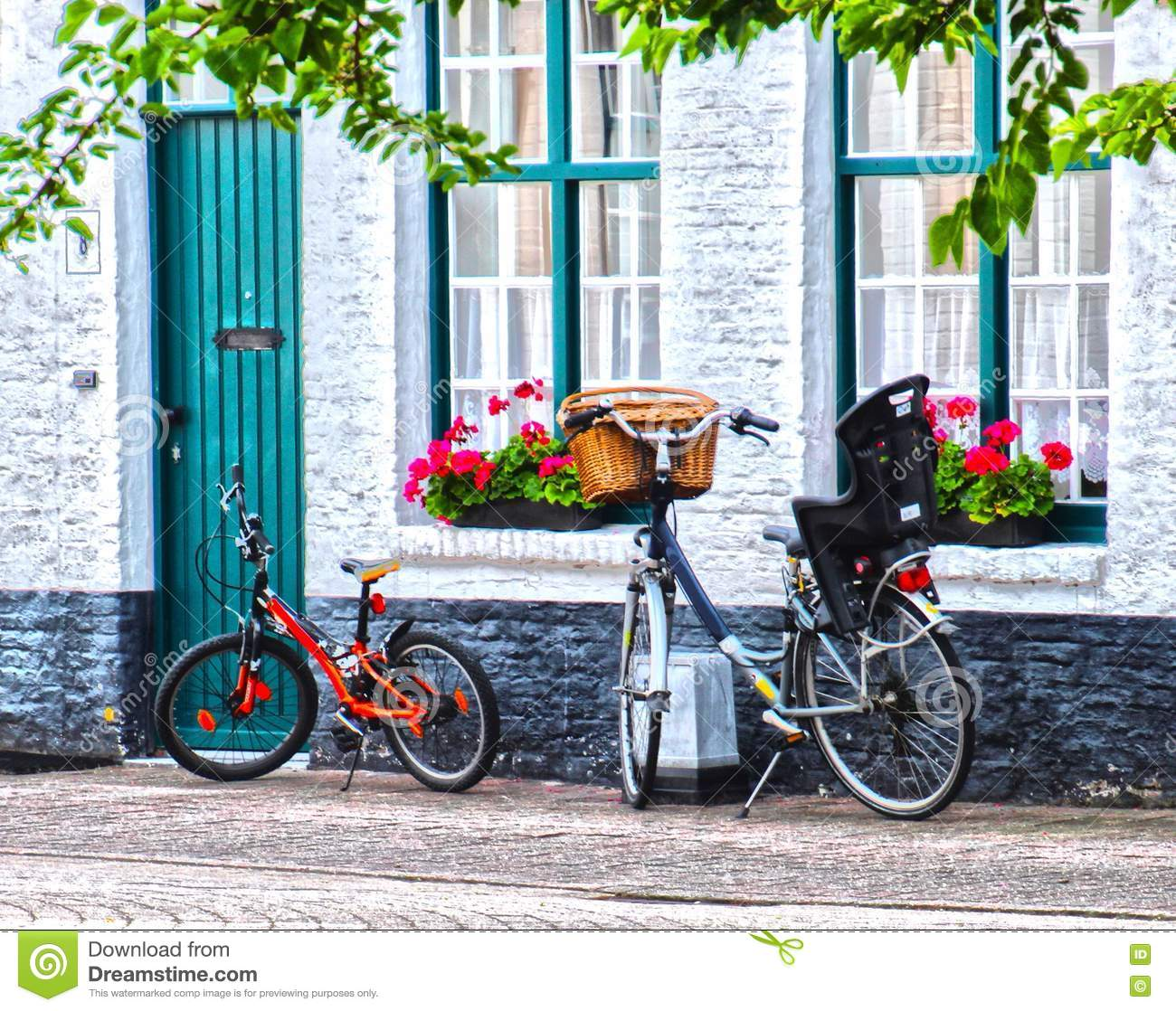 One black vintage style one red child size bicycle in front of the entrance of a white house on the street windows are green color