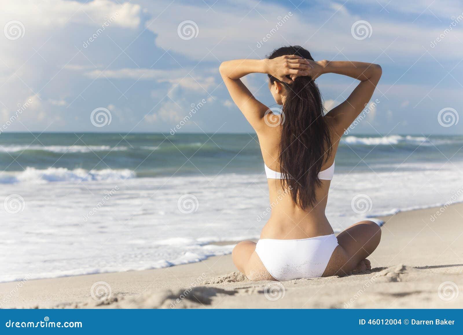 Bikini blanco que se sienta de la muchacha atractiva de la mujer en la playa
