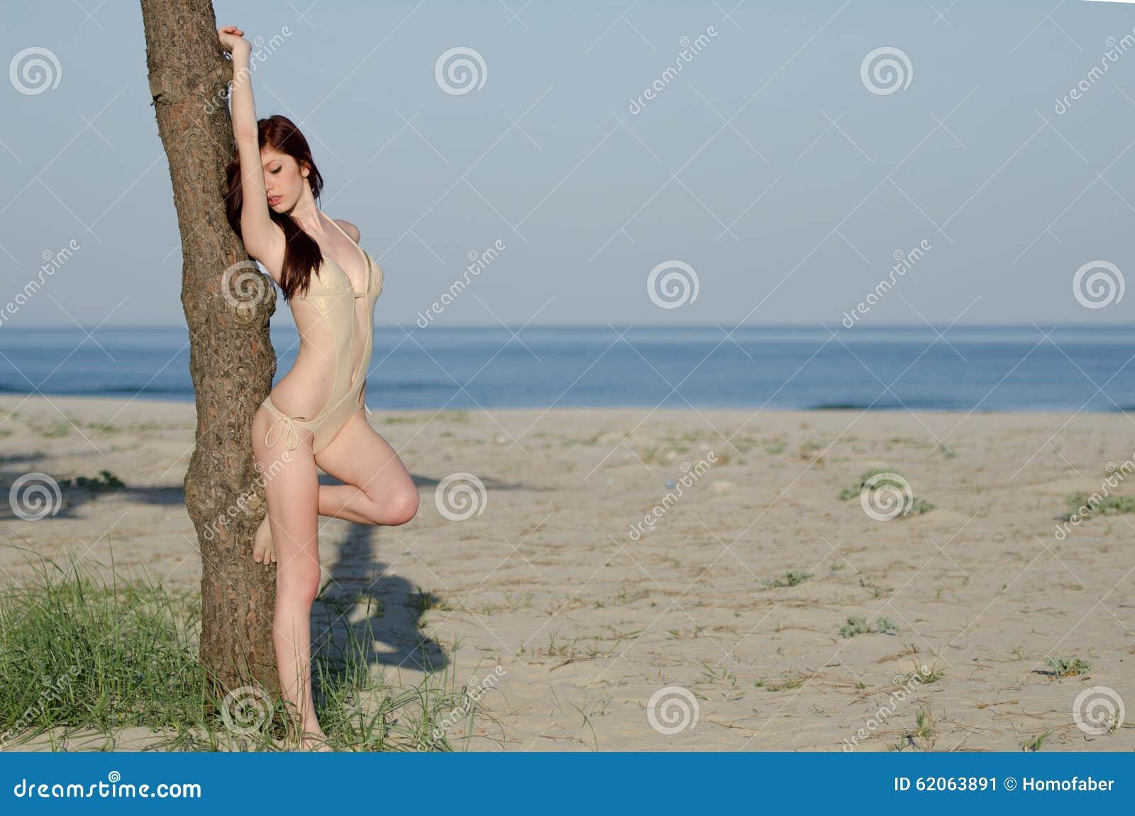 Bikini d uso della tuta della giovane donna rossa sexy dei capelli