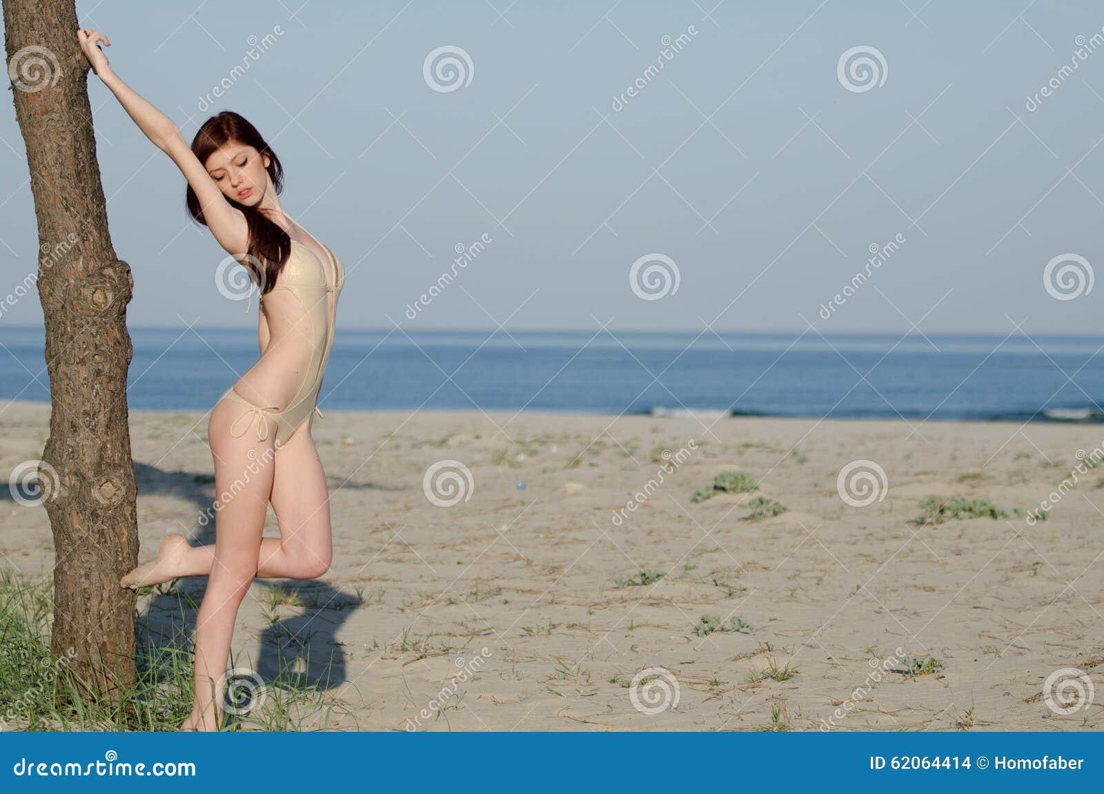 Bikini de la bata de la mujer roja joven atractiva del pelo que lleva