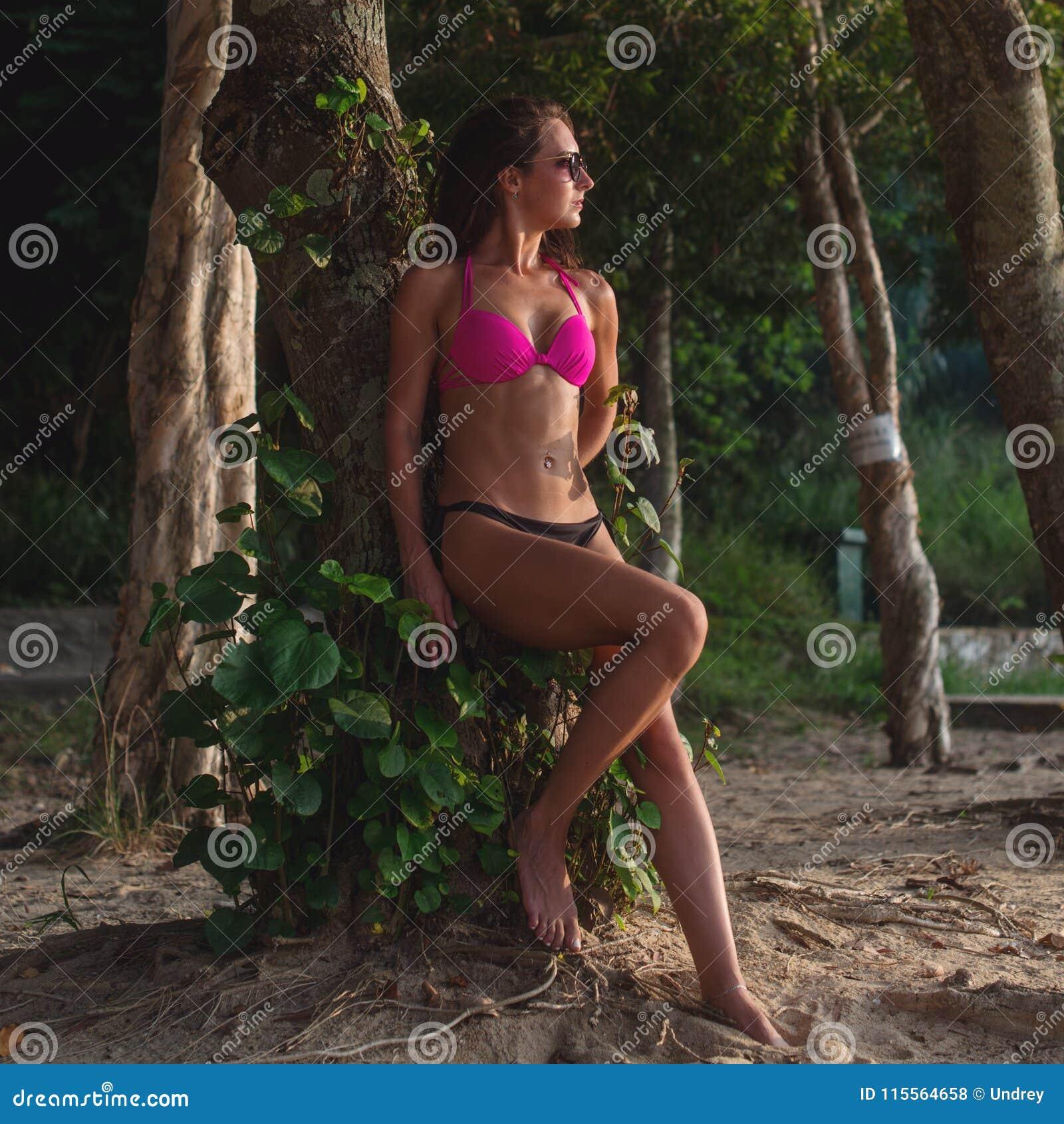 Bikini femminile ed occhiali da sole d uso di modello castana di forma fisica che pendono contro l albero che giudica i suoi cape