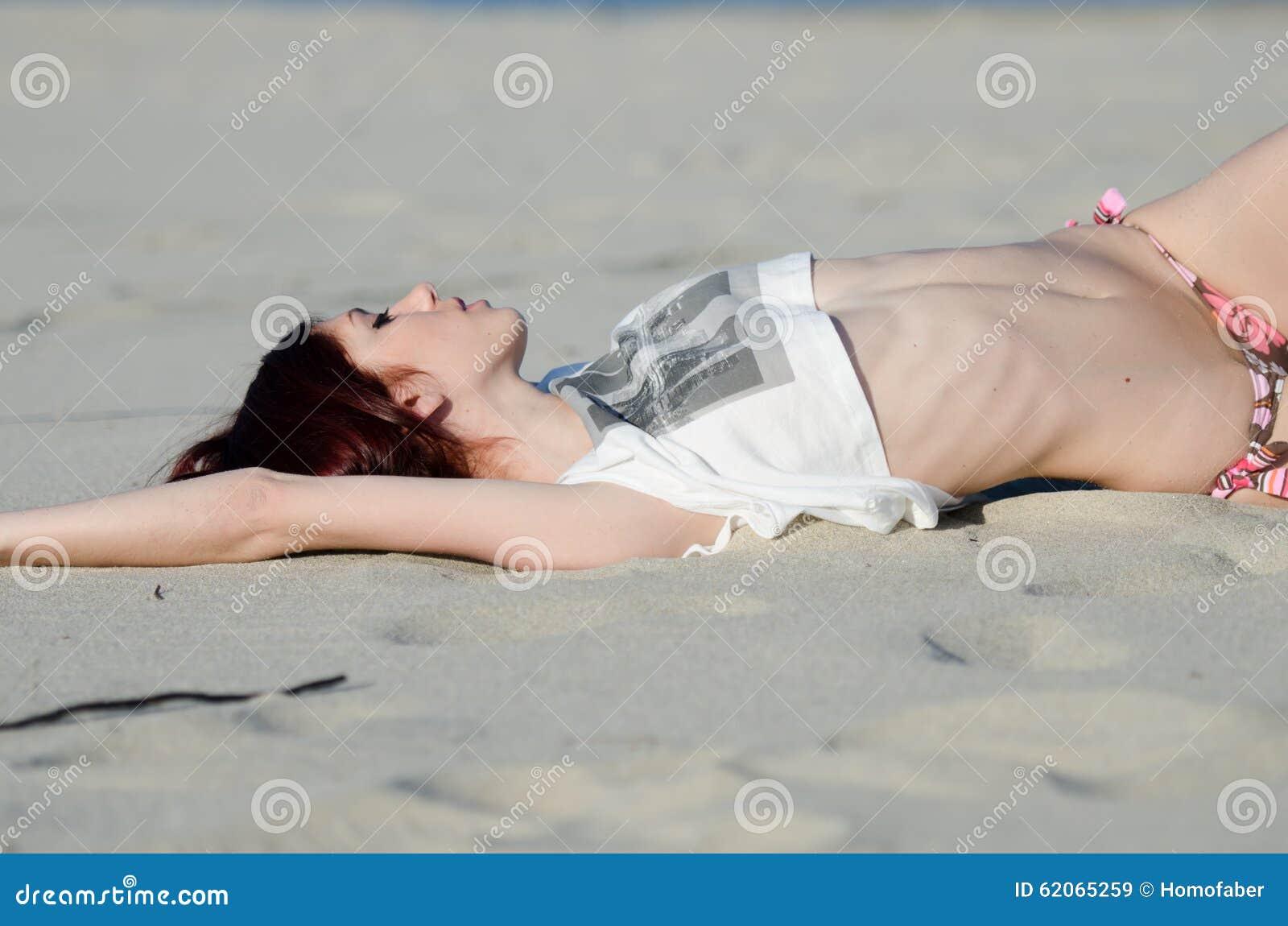 Bikini inferior que lleva y camisa de la mujer roja joven delgada del pelo