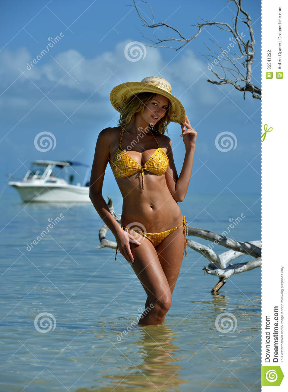 Bikini model in straw hat posing in front of camera at tropical beach location